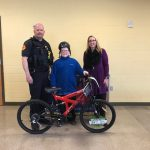 Student who won bike standing by Officer Oliver and Mrs. Kammeyer.